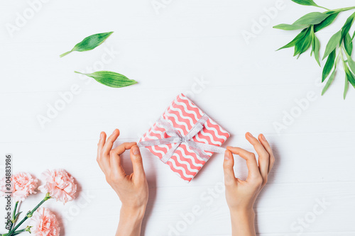 Woman's hands unwrapping small gift box Tablou Canvas