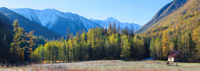 A picturesque valley in the Altai Mountains, an autumn panoramic view, there is a hut on the glade
