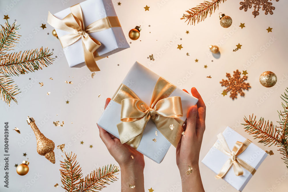 Fototapeta Female hands holding gold gift box on light golden background with flying Christmas decorations, fir branches, balls, sparkles and confetti. Xmas and New Year holiday, bokeh, light. Selective focus