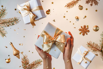 Female hands holding gold gift box on light golden background with flying Christmas decorations, fir branches, balls, sparkles and confetti. Xmas and New Year holiday, bokeh, light. Selective focus