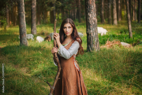 Canvas Print Young beautiful girl in medieval cowboy clothes, with a stick in hand
