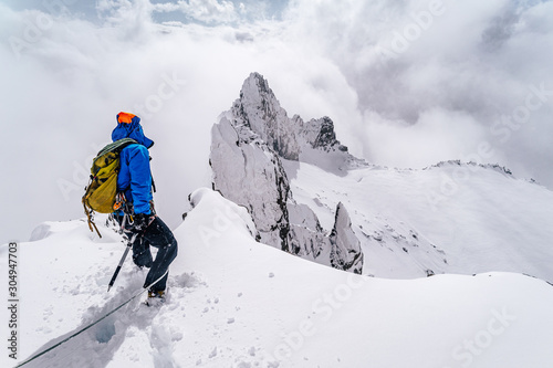 An alpinist climbing an alpine ridge in winter extreme conditions Wallpaper Mural