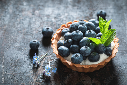 Tela Homemade mini tart with blueberries and whipped cream
