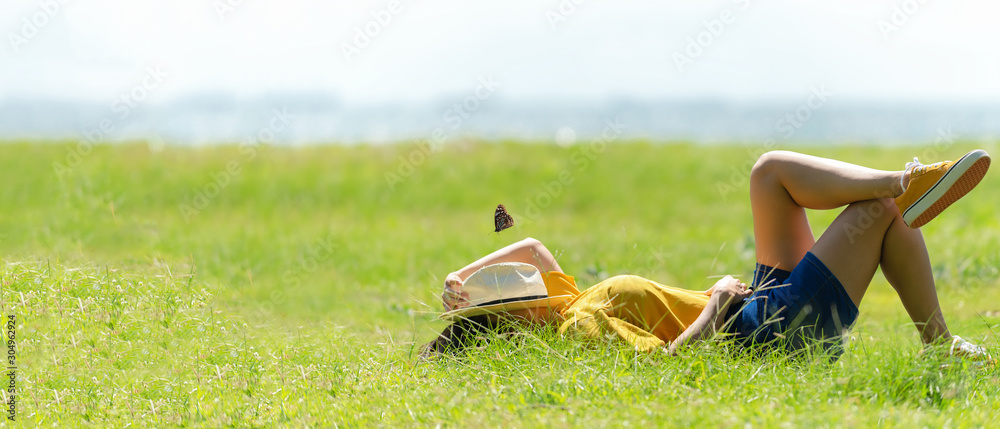 Fototapeta Woman relax and sleep chill  in the meadow  outdoor near sea beach.  Lifestyle and Vacations Concept