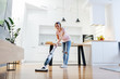canvas print picture - Full length of worthy caucasian blonde housewife using steamer to clean floor in living room.