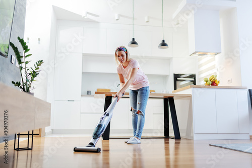 Fotografia Full length of worthy caucasian blonde housewife using steamer to clean floor in living room