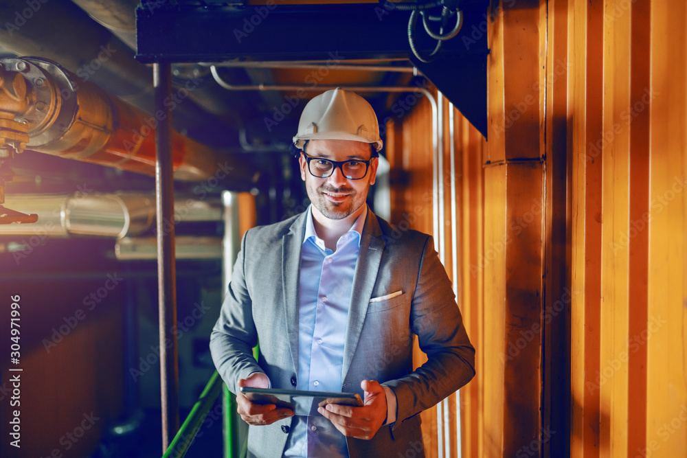 Fototapeta Manager in suit and with helmet on head standing in factory and holding tablet while looking at camera.