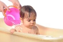 Happy Baby Girl Under Splashes Of Water In Bath