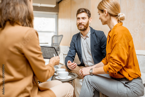 Obraz Young and lovely couple choosing a new house to buy, looking on the projects with a sales manager in the office of real estate agency - fototapety do salonu