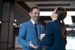 Two business partners smiling while joking and drinking morning coffee