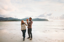Family Walking On Beach Vacation Couple Traveling With Baby Outdoor Healthy Lifestyle Activity Man And Woman Parents With Child Summer Trip In Norway