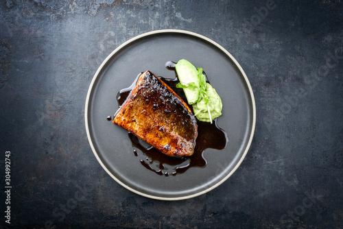 Fototapeta Minimalistic design Japanese salmon fish filet with vegetable and wasabi creme glazed in teriyaki sauce as closeup on a modern design plate obraz