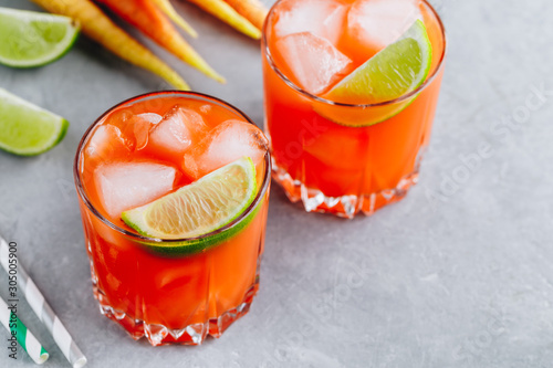 Obraz na plátně  Carrot Ginger Margarita cocktail with lime in glass