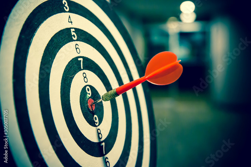 Fotografía  Red dart arrow  hitting in the target center of dartboard on bullseye for Business focus performance and target group concept