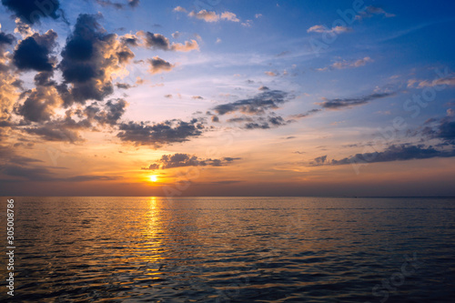 Amazing summer sunset view on the beach. Beautiful blazing sunset landscape at black sea and orange sky above it with awesome sun golden reflection on calm waves as a background.
