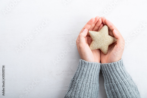 Recess Fitting India Christmas star decor in women hand. Christmas greeting card. Woman's hands hold christmas or new year decorated gift.