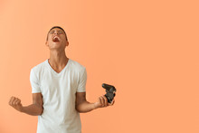 Emotional African-American Teenager Boy With Game Pad On Color Background
