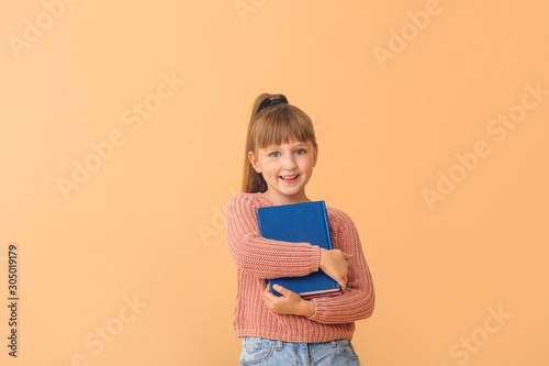 Fototapeta Cute little girl with books on color background obraz