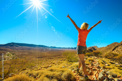 Fototapeta Woman enjoying views at Mount Sonder and Gosses Bluff crater at halfway point in Larapinta Trail, Ormiston Pound Walk