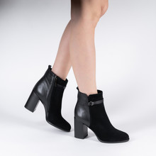 Black Leather Female High-heeled Ankle Boots On Model Legs Shooting In Studio On A White Background