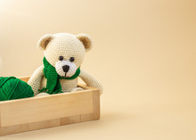 Crocheted Toy Bear In A Green Scarf On A Light Background