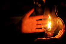 Hands Next To Oil Lamp