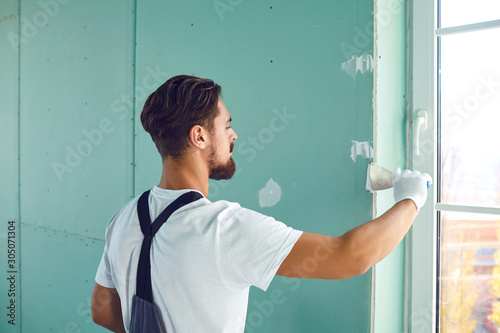Fotomural Worker builder plasterer plastering a wall of drywall at a construction site ind