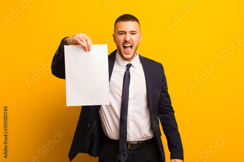 Obraz young handsome businessman  against flat background holding an empty piece of paper - fototapety do salonu
