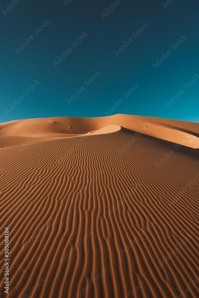 Fototapeta Vertical shot of a peaceful desert under the clear blue sky captured in Morocco
