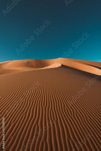Vertical shot of a peaceful desert under the clear blue sky captured in Morocco Fototapeta