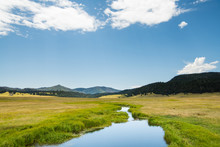 A Calm Stream Reflects A Beautiful Blue Sky As It Curves Through Lush Green Meadows In The Mountains Of Northern New Mexico