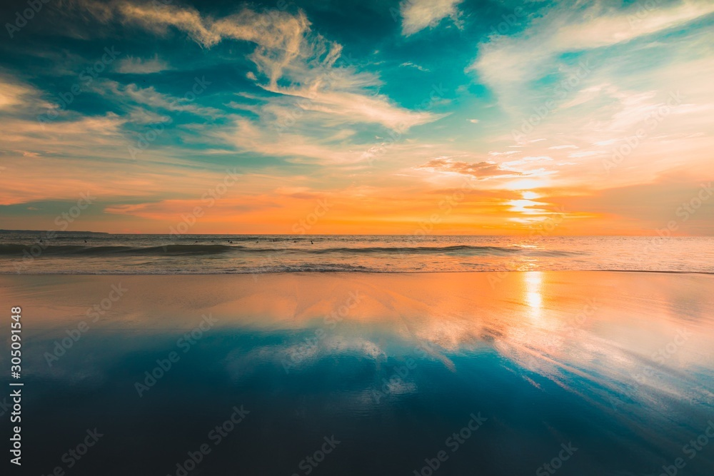 Fototapeta Breathtaking view of the reflection of the sun and the sky on the beach captured in Bali