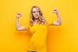 Leinwanddruck Bild - young pretty blonde woman feeling proud, arrogant and confident, looking satisfied and successful, pointing to self against flat color wall