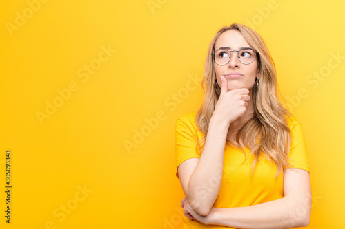 Leinwand Poster young pretty blonde woman thinking, feeling doubtful and confused, with differen