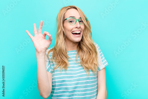 young pretty blonde woman feeling successful and satisfied, smiling with mouth wide open, making okay sign with hand against flat color wall