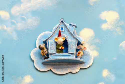 Doll mouse near the dollhouse on a blue background Wallpaper Mural