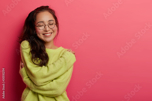 Photo Photo of charming woman expresses self love and care, enjoys wearing new soft gr