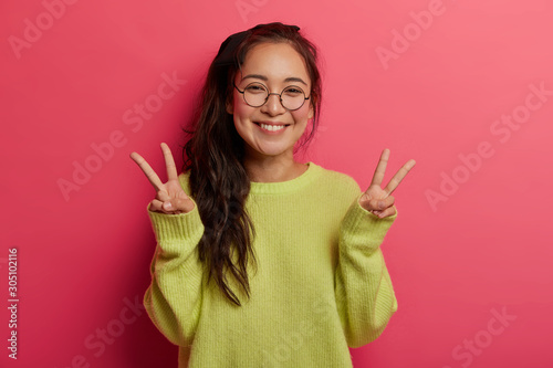 Lucky cheerful girl shows victory or peace gesture, enjoys awesome day, sends po Canvas-taulu