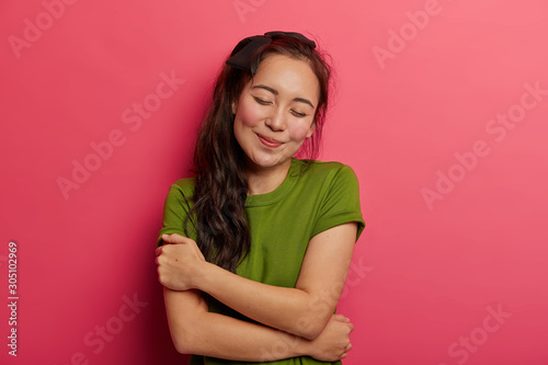 Stampa su Tela Tender cheerful girl with dark hair has romantic mood, embraces herself, tilts head, keeps eyes shut, likes own body, wears casual green t shirt, poses indoor