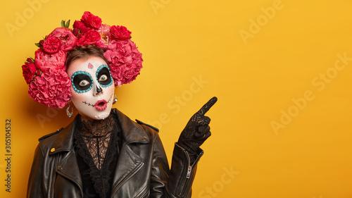 Fotografía Shocked female wears creative sugar skull makeup, wreath made of red peonies, ce