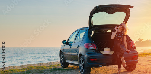Obraz na plátne Young woman sits in a car trunk by the sea on the beach