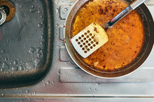 Dirty Greasy Steel Pan With Perforated Spatula. Placed On Top Of A Steel Kitchen Sink With Water Droplets All Around