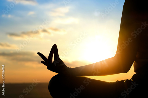 Fotografía Silhouette of a woman doing meditation on the beach of the sea during the morning hours