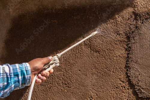 Worker sprays adobe wall with water Wallpaper Mural