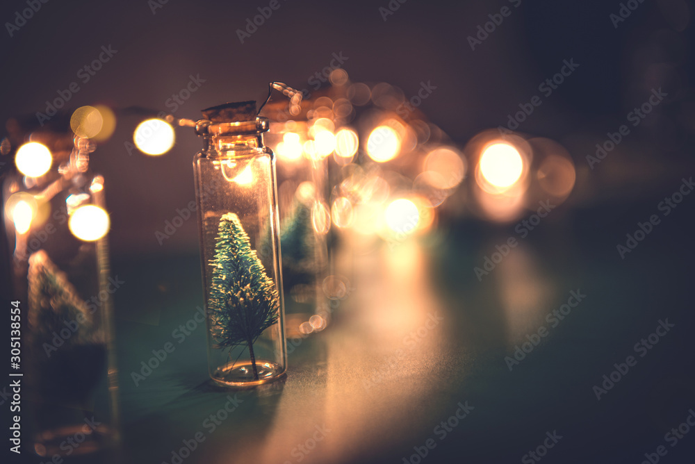 Fototapeta Close-up, Elegant Christmas tree in glass jar on green color background. copy space