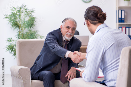 Fototapeta Old man visiting young male doctor psychologist obraz na płótnie