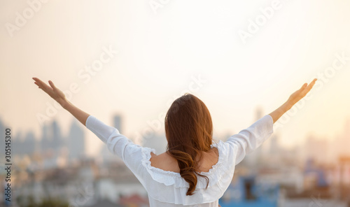 obraz dibond Asian woman raised hands up in the air over city background while standing at outdoor.