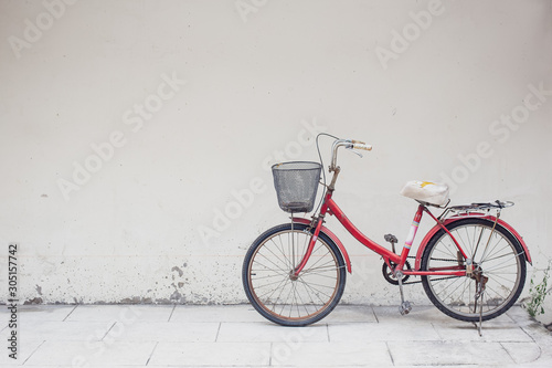 Recess Fitting Bicycle red bicycle with basket in front of the white wall, background