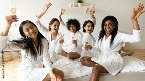 Poster de jardin Alcool Happy diverse young women raise champagne glasses look at camera