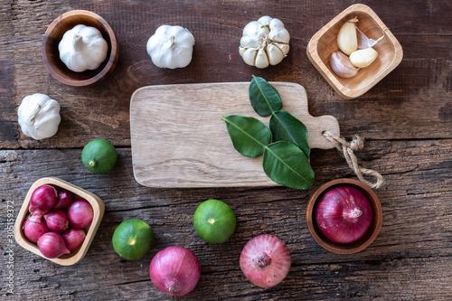 Cuadros en Lienzo  Top view of herbal vegetable ingredients, garlic, red onion, and empty chopping
